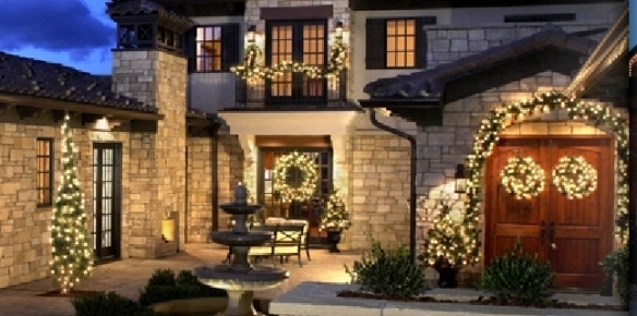 This breathtaking outdoor lighting holiday display uses multiple wreaths in this lighting design.
